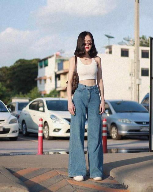 Chiếc quần jean ống rộng dài qua mắt cá nhân kết hợp với chiếc áo croptop ngắn