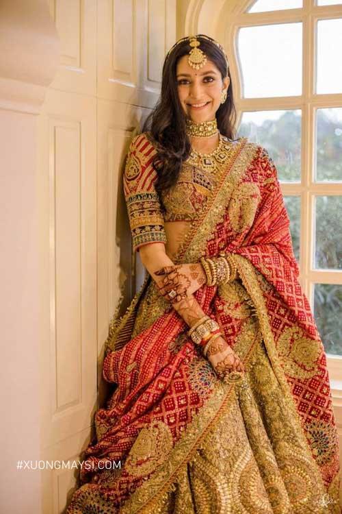 Các đường chỉ vàng thêm tỉ mỉ trên nền váy cưới đỏ làm chiếc váy vô cùng nổi bật